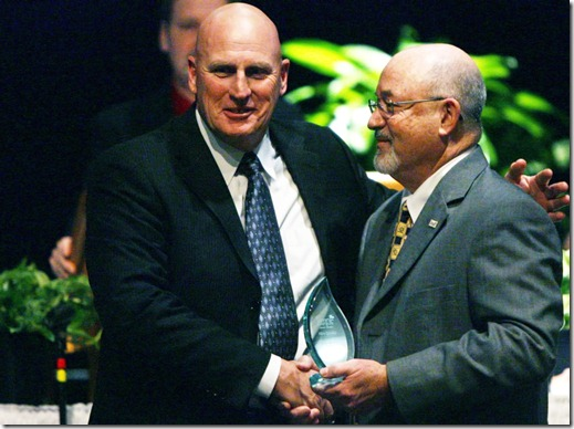 left Temple Head Football Coach and athletic director Mike Spradlin is presented an Impact Award by Dan Jones