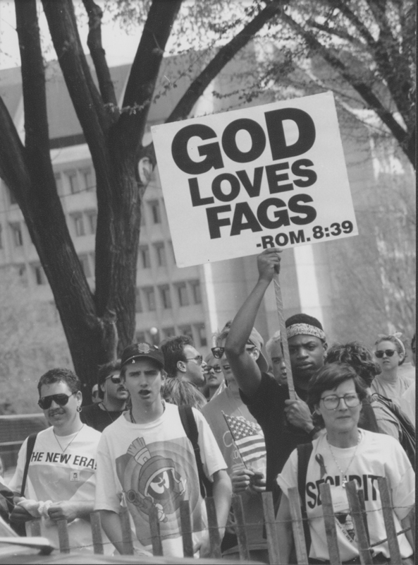 "Man holding a ""God Loves Fags"" sign at a demonstration, presumably at the March on Washington. 1993."