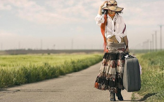 Mulher andando pela estrada com mala na m%25C3%25A3o._large