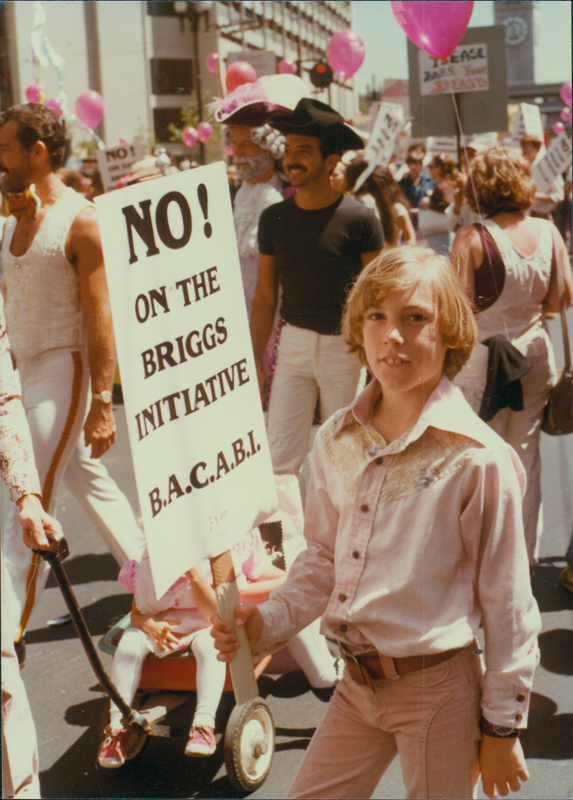 "Boy holds a Bay Area Coalition Against the Briggs Initiative (BACABI) ""No on the Briggs Initiative"" sign on Gay Freedom Day at the San Francisco pride parade. June 25, 1978."