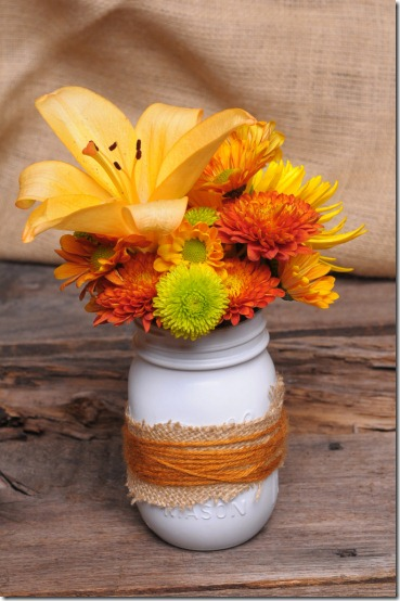 Painted mason jar wrapped with jute used as a vase for summer flower arrangements