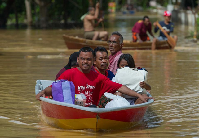 A family ride in a boat through floodwaters in Pengkalan Chepa, near Kota Bharu, Malaysia, on 26 December 2014. Photo: AFP Photo