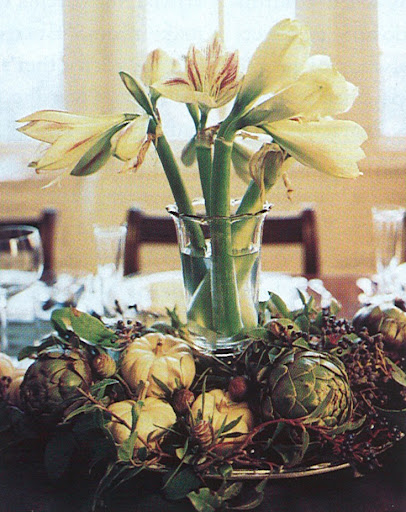 A centerpiece of amaryllis surrounded by artichokes and gourds.