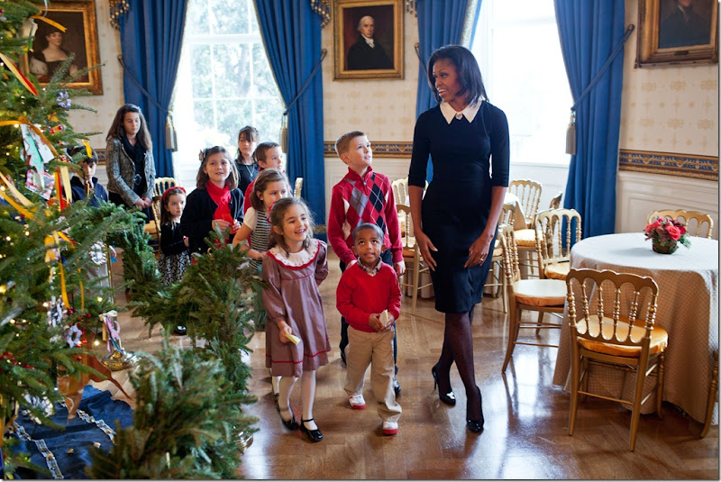 First Lady Michelle Obama walks with children past the official White House Christmas Tree in the Blue Room, Nov. 30, 2011. Mrs. Obama welcomed military families to the White House for for the first viewing of the 2011 holiday decorations. (Official White House Photo by Lawrence Jackson)<br /><br />This official White House photograph is being made available only for publication by news organizations and/or for personal use printing by the subject(s) of the photograph. The photograph may not be manipulated in any way and may not be used in commercial or political materials, advertisements, emails, products, promotions that in any way suggests approval or endorsement of the President, the First Family, or the White House.&nbsp;