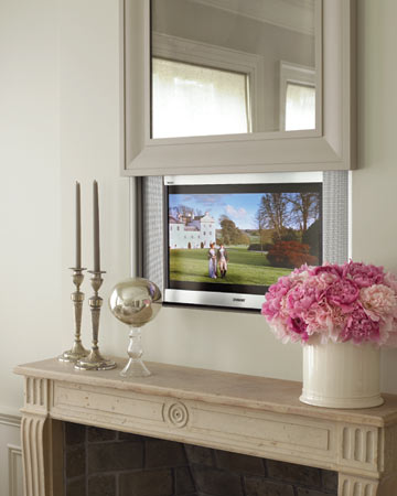 A television is over the living room mantel; an antiqued mirror lifts to reveal it.