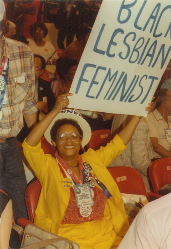 "Lesbian & Gay Caucus member holds a sign that reads ""Black Lesbian Feminist"" at the1980 Democratic National Convention at Madison Square Garden in New York City. August 11- 14, 1980."