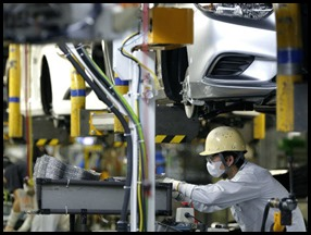 Operário trabalha na autoindústria de Tóquio: governo japonês está pedindo que companhias lucrativas aumentem salários