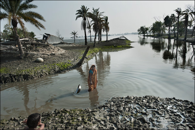 A woman stood where her house was before Cyclone Aila destroyed it in 2009. Scientists expect rising sea levels to submerge 17 percent of Bangladesh's land and displace 18 million people in the next 40 years. Photo: Kadir van Lohuizen / The New York Times