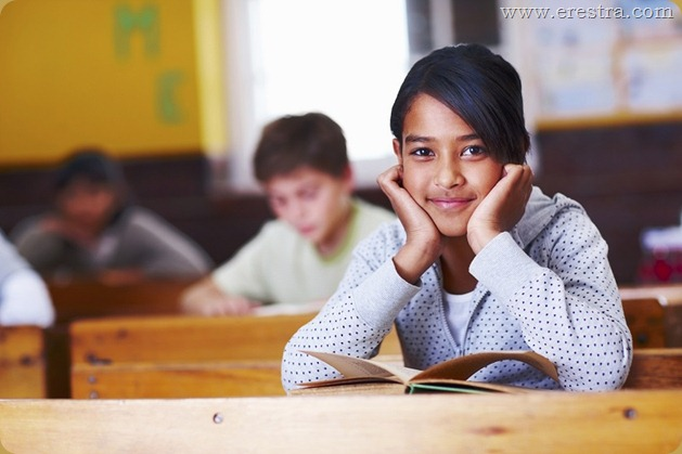 Little Asian girl in her classroom, studying