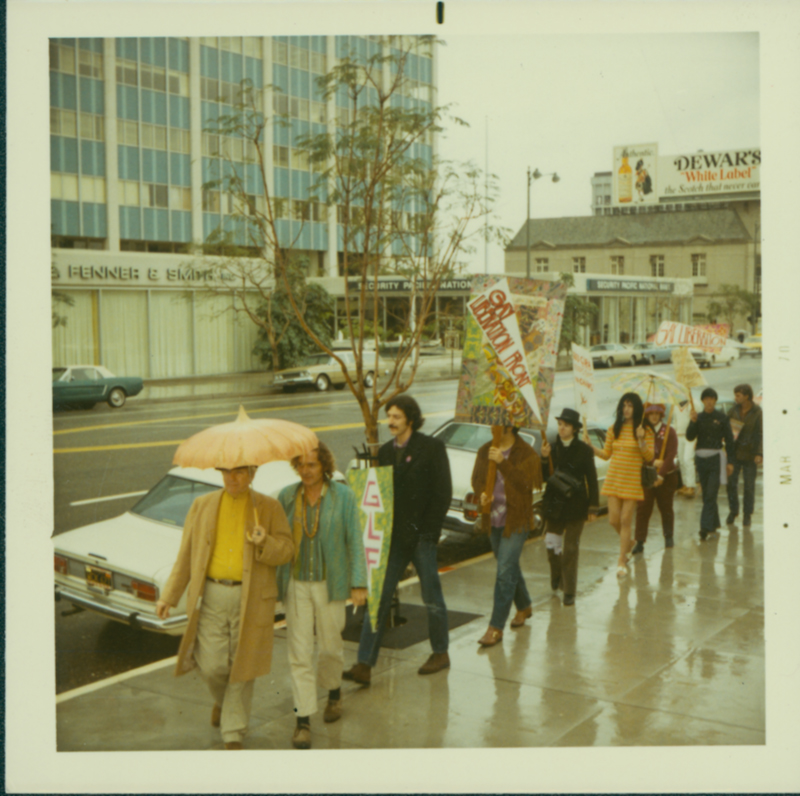 Morris Kight (yellow shirt & umbrella) leads a Gay Liberation Front protest on the streets regarding the first gay pride parade permits. June 1970.