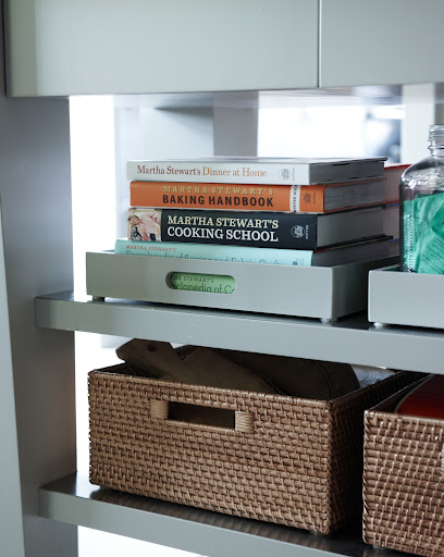 Bins and baskets are a great way to organize cookbooks and other items on exposed shelves.