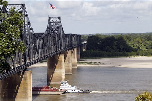 A towboat and its barges pass under the old Mississippi River bridge at Vicksburg, Miss., Thursday, 26 July 2012. In a switch of extremes, the river has dropped to very low levels this summer unlike last year when the river was flooding much of the Delta due to record high levels. The drop in water level now exposes the river bottom, forcing river traffic to a trickle as barges are forced to lessen their loads to keep from getting stuck on sandbars. Rogelio V. Solis / AP Photo