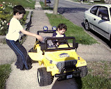 Kai and Eidan riding on the neigbor's battery powered mini Jeep
