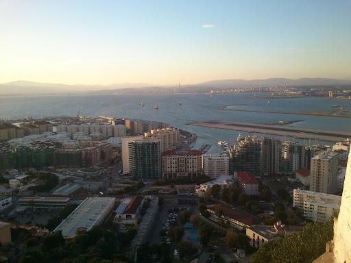 Trangt om saligheten. Flere postboksfirmaer enn innbyggere. Røyking i hotellbarer og lav skatt. Gibraltar er et fristed for gamblingselskaper og engelskmenn som holder fast i den siste koloni på det europeiske fastlandet. Gibraltars flystripe opp til høyre. Når flyene kommer fra England stenges veien inn til Gibraltar - som er over samme flystripe.
