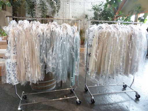 No, these are not the bridesmaids' dresses. The racks are filled with linens from La Tavola. Since the floorplan was set out in a confetti pattern, there were multiple table sizes, and three different linen options to add dimension.