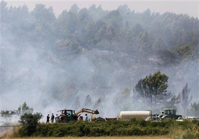 Farmers try to put out a fire near Llers, in the Spanish province of Girona, 23 July 2012. Albert Gea / REUTERS