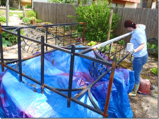 Katie base coat painting the rusted arbor.