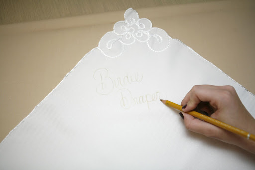 Step 1: With the pencil, trace out the guest's name and table number. It'll serve as your stitching guide.
