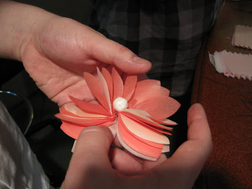 This flower is made with a stack of paper cut into the shape of an 8, with wire twisted in the middle to form a stem.  The center ball, already on a wire, gets twisted on and then petals get fanned out.