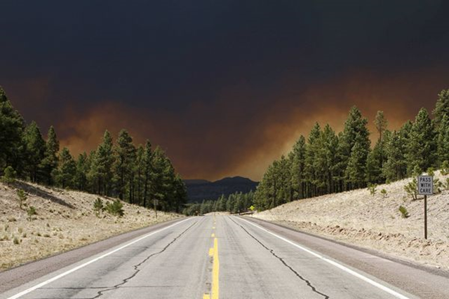 A wildfire blackens the sky above U.S. Route 180 in Luna, New Mexico, on 6 June 2011. Joshua Lott / Reuters