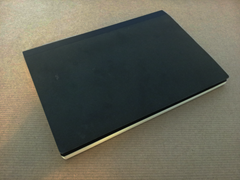 Closed notebook, with plain black cover and black enpapers just visible.
