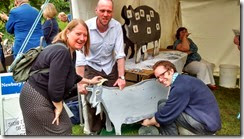 Rob White, Josh Williams and Jenny Hicks milking a goat