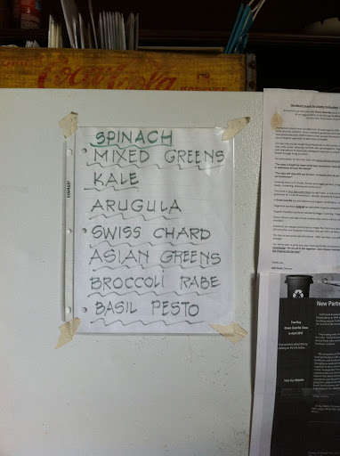Handwritten sign on the barn fridge advertises the day's greens.