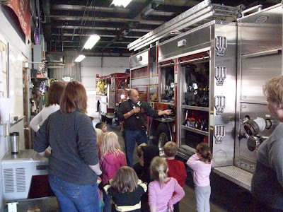 Firefighter Joe Redlinger shows equipment to children from the First Baptist Preschool.