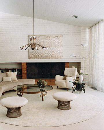 This living room features circular shapes, including a sofa by Modernica, Warren Platner stools, and a chandelier by Gaetano Scolari, all in a snowy-white hue.