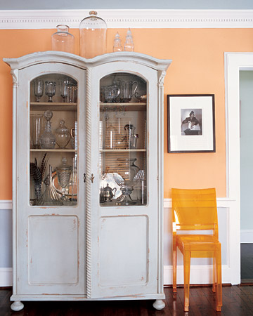 In this living room, Philippe Starck chairs sit next to a weathered celadon cabinet. The pale-orange walls unite this unexpected pair.