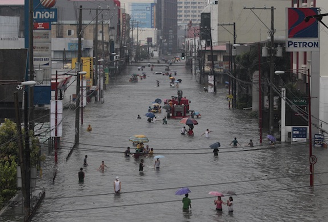 Filipinos wade through a flooded street at the financial district of Makati, south of Manila, Philippines, on Tuesday, 20 August 2013. Photo: Aaron Favila / AP