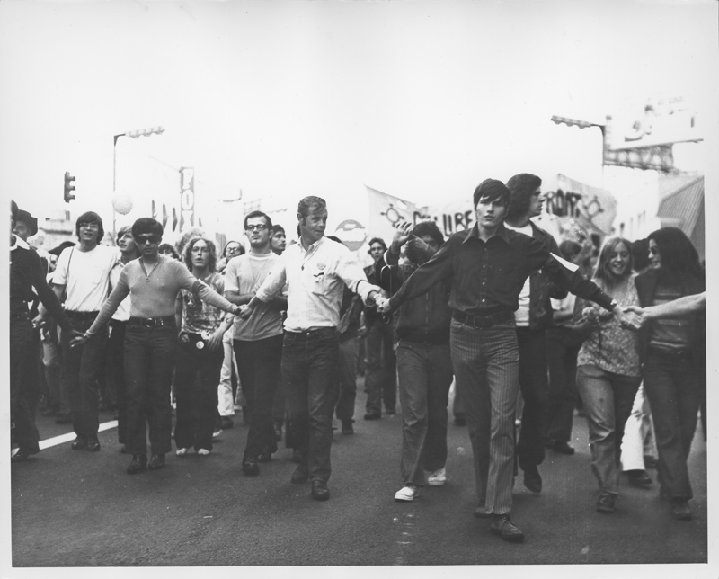 Crowd holds hands at the Los Angeles Christopher Street West pride parade. 1971.