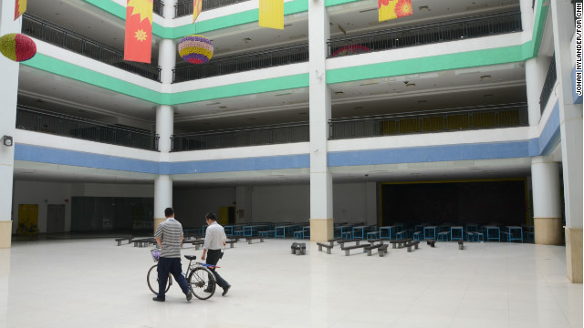 Two men walking through the empty South China Mall mall in a space planned for restaurants. Photo: CNN