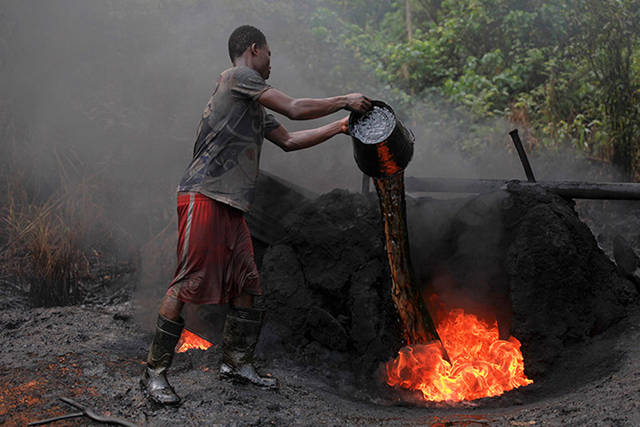 A labourer feeds a fire with crude oil at the illegal refinery. The Nigerian government's military crackdown against the theft of crude in the Niger River delta has left more than a 1,000 makeshift refineries in flames, worsening pollution in the area Photo: Akintunde Akinleye / Reuters
