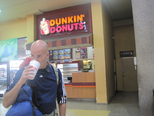Just like home - Erik enjoys a cup of Dunkin Donuts coffee at the Panama City bus station.