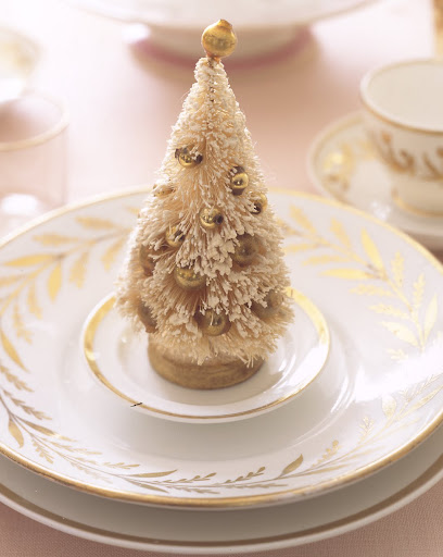 Having a snowy tree decorated with golden ornaments is the perfect touch to your table top.