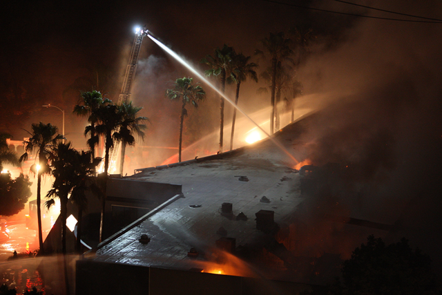 Firefighters spray water on a building set aflame by a wildfire on 14 May 2014, in Carlsbad, California. Photo: U.S. News & World Report