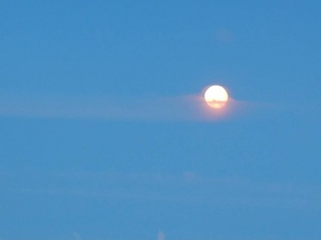 A line of upper atmospheric smoke passes across the face of the moon on the night of 6 July 2012. This photo was taken out of the window of the airplane en route from St. Petersburg to Krasnoyarsk. Smoke that reaches the upper atmosphere often travels long distances. This smoke has the potential reach North America within a few days. Jon Ranson