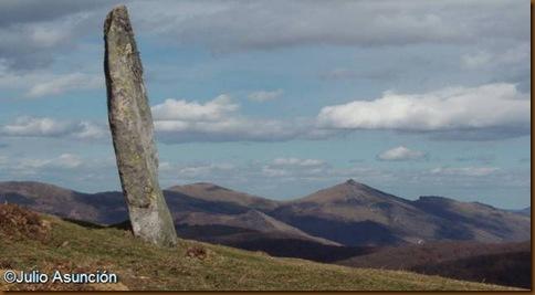 Vista lateral del menhir de Iruñarri - Al fondo el Mendaur