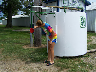 Mackenzie Adrian, 4-H County Council member, finalizes the paint job Thursday afternoon in preparation for Monday's Dunk Tank grand opening.  Photo Courtesy of the Washington County Extension.