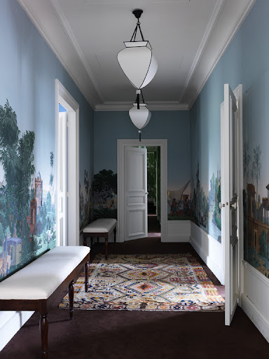 This cool-toned, exotic wallpaper by Zuber and a contrasting bold rug instantly transport and mesmerize all who enter; white trimmings keep the colorful accents polished and clean.