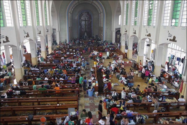 After Tyhoon Haiyan struck the Philippines, people took refuge in a Catholic church converted to a disaster relief centre in Tacloban City, 10 November 2013. The Philippines faced a humanitarian crisis days after the typhoon hit much of the Visayas with 1.9 million homeless and more than 6,000,000 displaced. In Tacloban alone, ninety percent of the structures are either destroyed or damaged. Photo: IBT