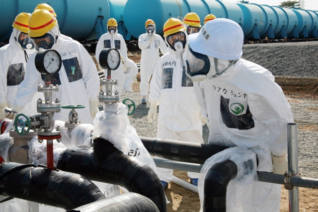 Nuclear Regulation Authority (NRA) Secretary General Shunichi Tanaka (R, w/white helmet) inspects the radioactive water-leaked plumbing with Tokyo Electric Power Co. (TEPCO) officials at the Fukushima Dai-Ichi nuclear power plant in Okuma in Fukushima prefecture, on 13 April 2013. Photo: JIJI PRESS / AFT / Getty Images