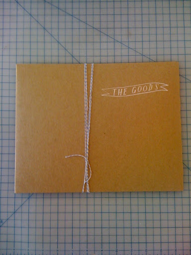 I love the combination of craft, clean white calligraphy, and blue baker's twine. What a great idea for invitation or favor packaging!