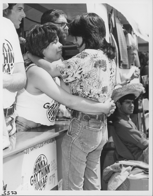 Lesbian women embrace at the Los Angeles Christopher Street West pride festival Gay Think booth. June 1975.