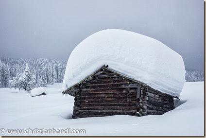 Heuschober mit viel Schnee am Dach an der Langlaufloipe Leitertal