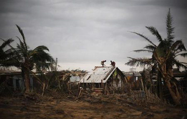 Fishermen and their family members repair the roof of their houses at the cyclone-hit Nalianuagaon village in Ganjam district in Odisha 15 October 2013. Photo: Adnan Abidi / REUTERS
