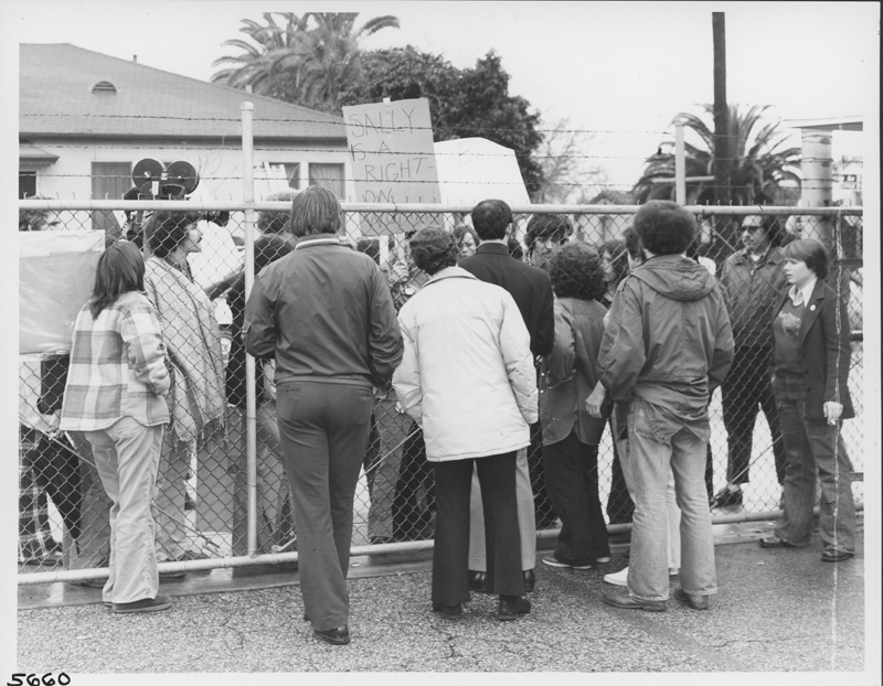Picketers at KCOP studios pass food, cigarettes and kind words to demonstrators inside the studio fences. Following negotiations, the studios accepted the demonstrators' demands. 1975