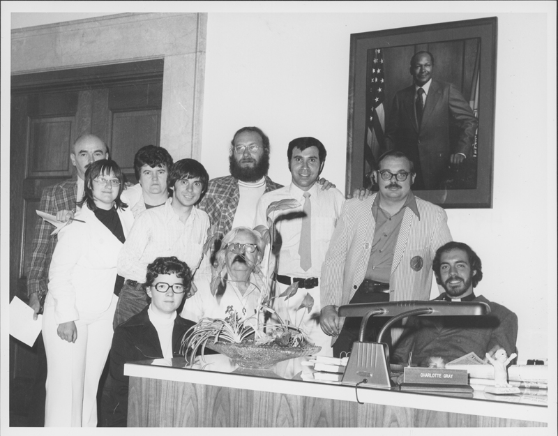 Gay and lesbian leaders visit Los Angeles Mayor Tom Bradley. The contingent includes from left (standing) Jim Kepner, Ann Montague, Pat Underwood, Frank Zerilli, Walt Blumoff, Pat Rocco, and Dave Glascock, and (crouching/sitting) Sharon Cornelison, Morris Kight, and Bob Sirico. 1974.