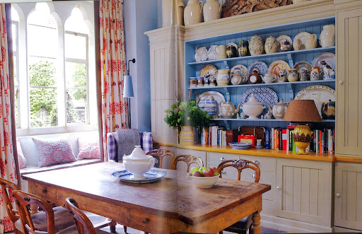 William Yeoward's country home kitchen features a window seat, piled with cushions, plus a rustic oak table.